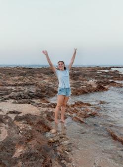 Счастливая девочка-подросток, стоящая на скале у моря на закате, в голубой футболке, джинсовых шортах и подняв руки вверх. макет футболки