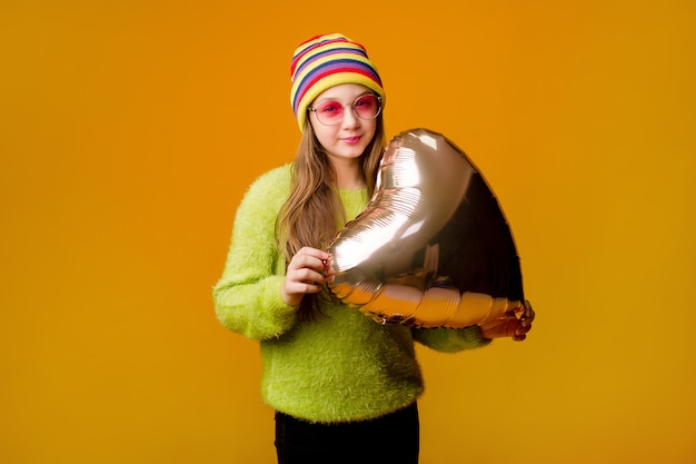 Happy teenage girl in sunglasses holds a heart-shaped balloon