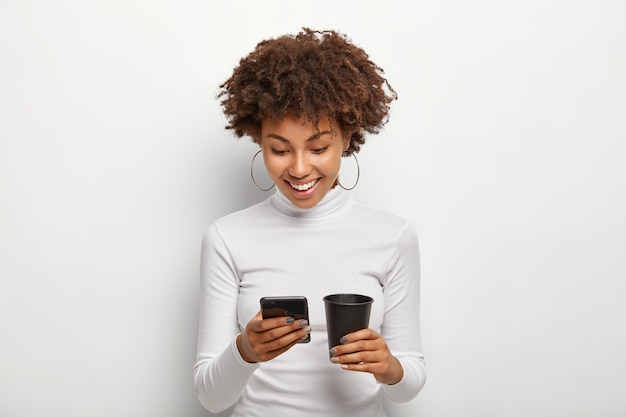 Happy teenage girl surfes internet on mobile phone, connected to free wifi, drinks takeout coffee, wears casual turtleneck jumper