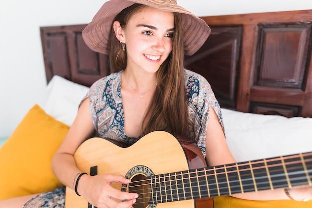 Happy teenage girl wearing hat playing guitar