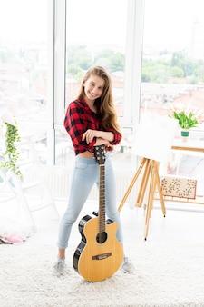 明るい部屋でギターを持つ幸せな 10 代の少女
