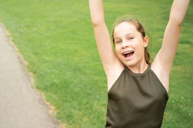 Happy teenage girl with hands up, against green summer park. confident young woman portrait copy space