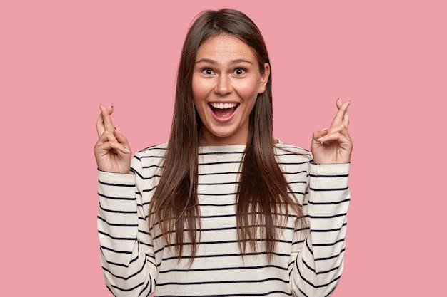 즐거운 표정으로 행복한 십대 소녀는 넓은 미소를 지으며 손가락을 교차하며 행운을 기대합니다.