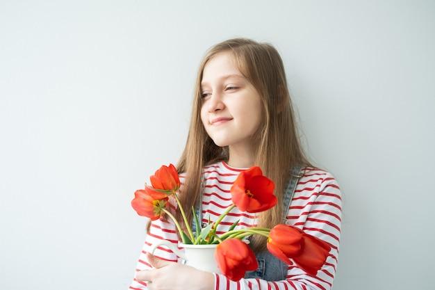 白い壁に立っている赤いチューリップと花瓶を保持している長い髪の幸せな10代の少女