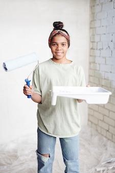 Счастливая девочка-подросток с роликом и белым контейнером с краской стоит перед камерой против угла у двух стен гостиной
