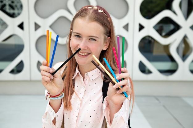 도시의 예술 공간에서 연필을 들고 분홍색 머리를 한 행복한 10대 소녀