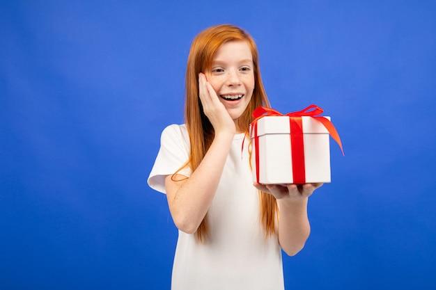 Счастливая девочка-подросток с рыжими волосами получила подарок на день рождения синего цвета