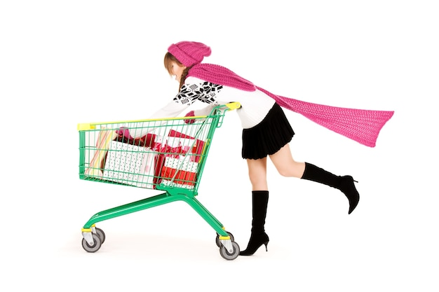 白い壁の上のショッピングカートと幸せな10代の少女