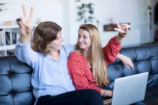 Счастливые девочки-подростки, сидя на диване с ноутбуком делают знак победы