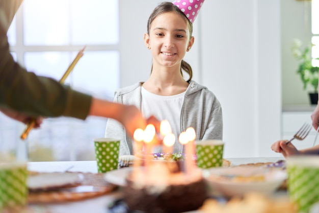 버트데이 모자를 쓴 행복한 10대 라틴 소녀는 집에서 가족과 함께 생일을 축하하는 동안 웃고 생일 케이크를 바라보고 있습니다. 아이, 축하 개념