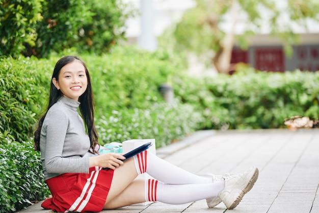 地面に座って、タブレットコンピューターでアプリケーションを使用して幸せな10代の女子高生