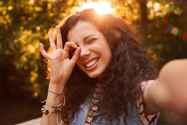 幸せな10代の女性、屋外を歩いて自分撮り写真を撮りながらokサインを介して