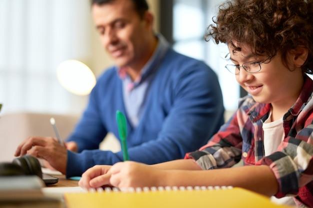 父親と一緒に机に座って、屋内で宿題をしながらメモをとっている眼鏡をかけた幸せな10代のラテン系の少年。オンライン教育、ホームスクーリングの概念