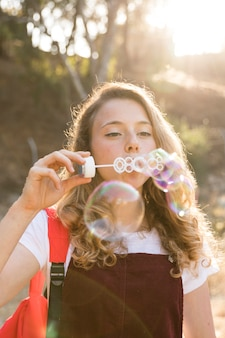 Happy teenager blowing bubbles in park