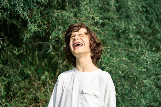 顔ににきびを持った幸せな10代の少年、歯列矯正器を身に着けて笑っている。ぎこちない年齢の概念。