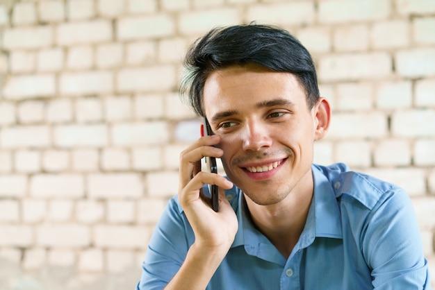 행복 한 십 대 w의 배경에 전화 근접 촬영 백인 젊은 갈색 머리 남자에 통신...