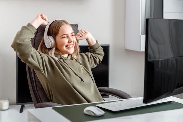 Счастливая девушка-подросток-киберспортсмен-геймер выигрывает в компьютерной онлайн-игре в одиночестве дома в свободное время. молодая блондинка в наушниках радуется победе в видеоигре, онлайн-победе.