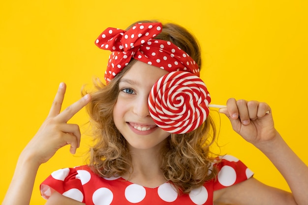노란색 벽에 빨간 막대 사탕을 들고 행복 한 십 대 소녀