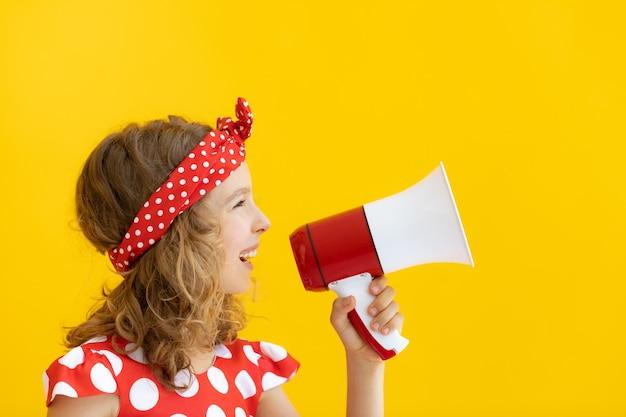 노란색 벽에 빨간색 스피커를 들고 행복 한 십 대 소녀