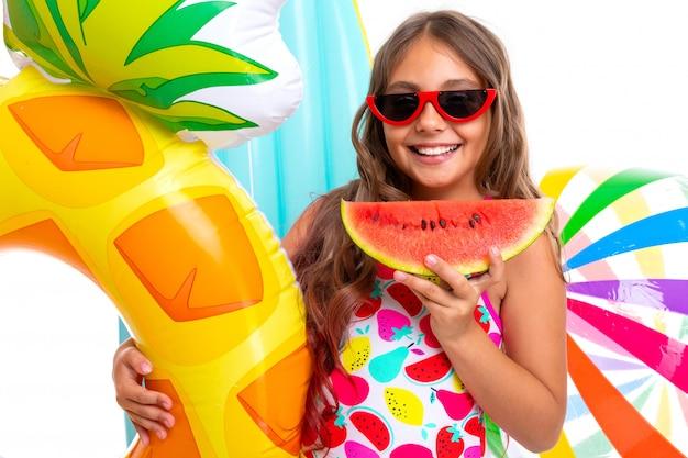 Счастливая девушка-подросток на летних каникулах у моря с плавательными кругами на белом фоне