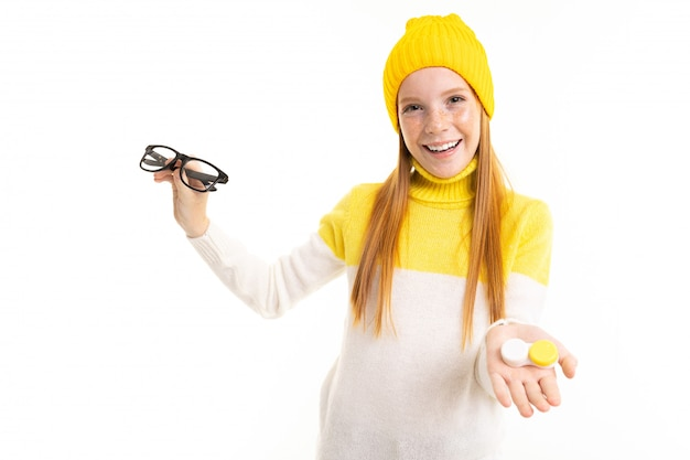 Happy teenager girl with red hair, hoody and hat holds a glasses isolated on white