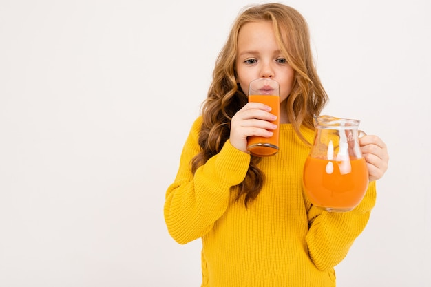 Happy teenager girl with red hair, hoody and yellow trousers drinks carrot juice isolated on white background