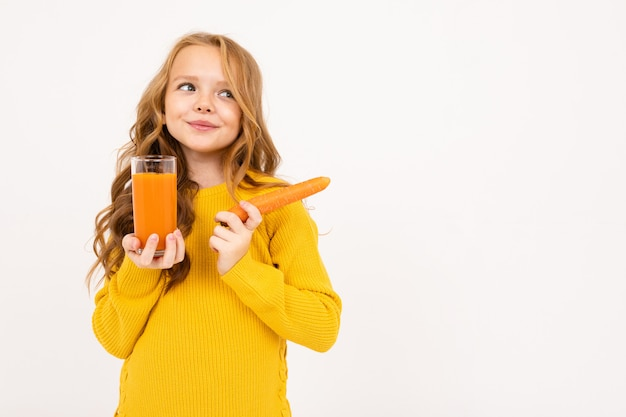 Happy teenager girl with red hair, hoody and yellow trousers drinks carrot juice isolated on white