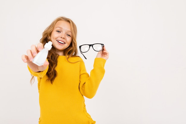 Happy teenager girl with red hair, hoody and yellow trousers holds contact lenses and glasses isolated on white