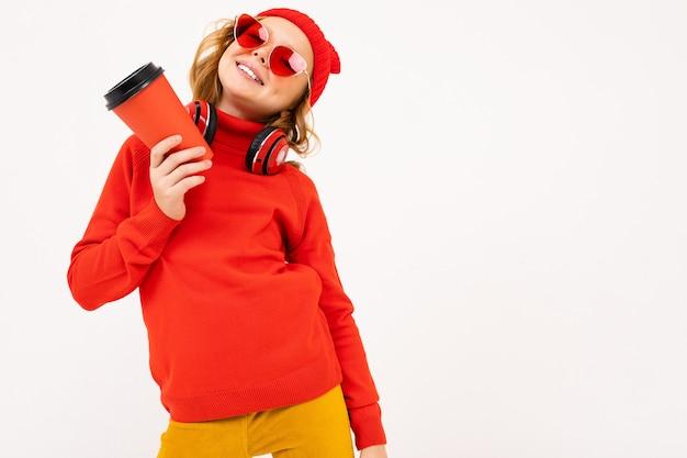 赤い髪と幸せなティーンエイジャーの女の子、赤いメガネ笑顔と白い背景で隔離のコーヒーを飲む