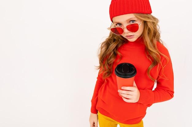 赤い髪と幸せなティーンエイジャーの女の子、赤いメガネ笑顔と白で隔離コーヒーを飲む
