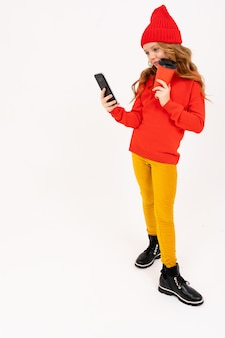 Happy teenager girl with red hair, red hat, hoody and yellow trousers smiles, drinks coffee and play phone games isolated on white background
