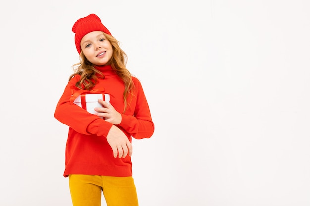Happy teenager girl with red hair, red hat, hoody and yellow trousers smiles and holds a gift isolated on white