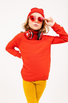 Happy teenager girl with red hair, red hat and sunglasses posing with earphones isolated on white background