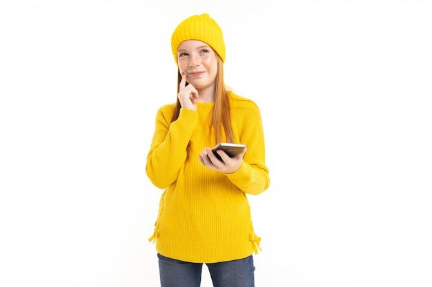赤い髪、黄色のフーディ、ズボンと幸せなティーンエイジャーの女の子が電話と白い背景で隔離の笑顔と通信します。