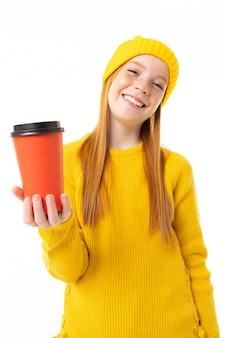 赤い髪、黄色のフーディ、ズボンと幸せなティーンエイジャーの女の子は、白い背景で隔離のコーヒーのカップを保持しています。
