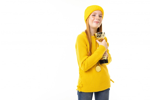 赤い髪、黄色のフーディ、ズボンと幸せなティーンエイジャーの女の子を白で隔離されるゴールドカップを保持しています。