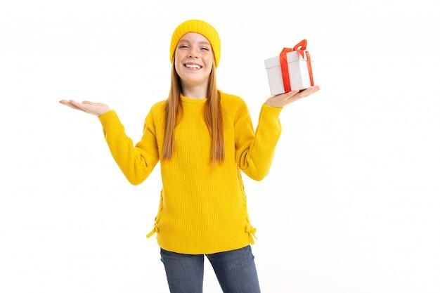 赤い髪、黄色のフーディ、ズボンと幸せなティーンエイジャーの女の子は白で隔離のギフトと白いボックスを保持します
