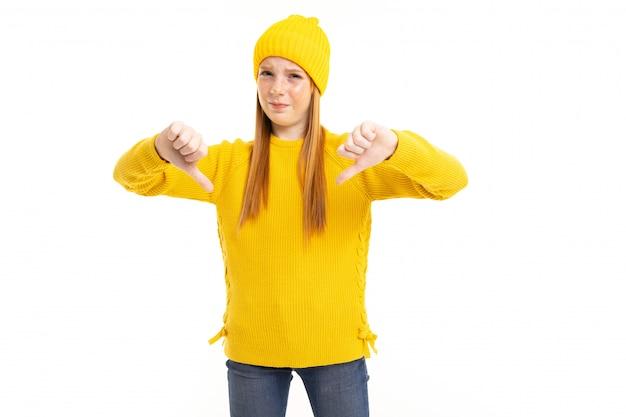 赤い髪、黄色のフーディ、ズボンと幸せなティーンエイジャーの女の子は白い背景に分離された悪いを示しています