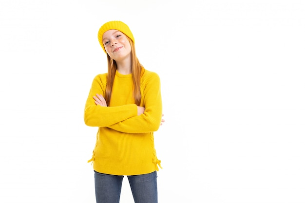 赤い髪、黄色のフーディ、ズボンと幸せなティーンエイジャーの女の子は白い背景に分離された何か良いことを考えています
