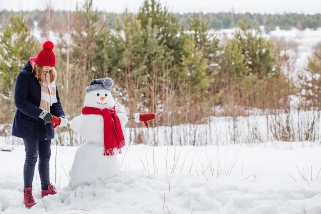 Счастливая девушка-подросток со снеговиком в зимнем лесу