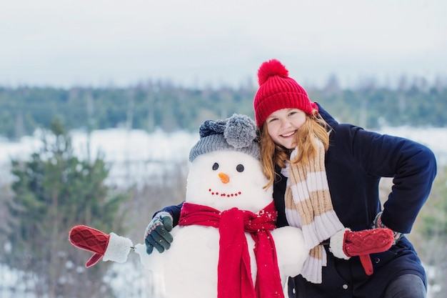 Happy teenager girl with snowman in winter forest