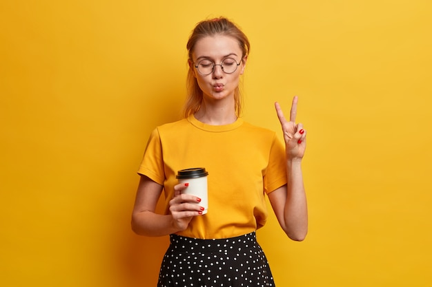 행복한 십대는 실내에서 재미 있고, 입술을 접고, 눈을 감고, 평화 제스처를 만들고, 커피를 마시고, 밝은 노란색 티셔츠를 입고, 광학 안경을 쓰고, 실내 포즈를 취합니다.