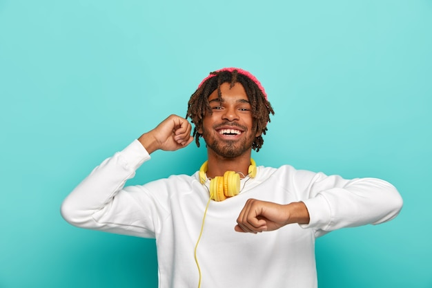 Happy teenager has short dreadlocks, moves in rhythm of music, feels pleasure, dressed in white sweater, isolated over blue background