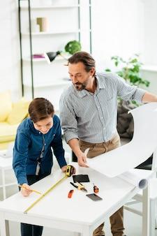 感情的な好奇心旺盛な父親が大きな画用紙を手に持って近くに立っている間、テーブルの巻尺を見て幸せなティーンエイジャー