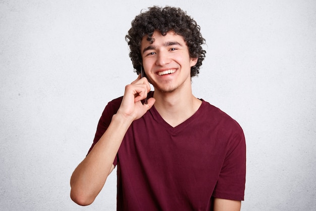 Счастливый подросток или хипстер, говорит по мобильному телефону с лучшим другом