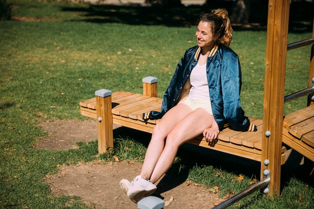 Happy teenager sitting on bench in park