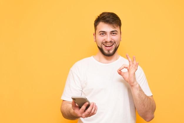彼の手でokの標識を示す彼の手でスマートフォンを保持している白いtシャツを着て幸せなティーンエイジャー