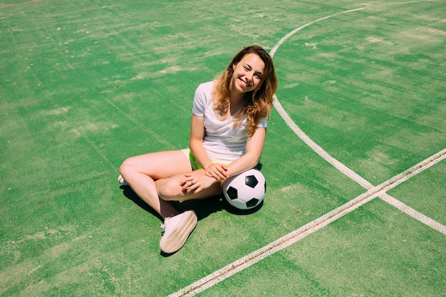 Happy teenager with ball on football pitch