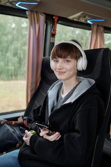Счастливый подросток со смартфоном, слушать музыку в наушниках