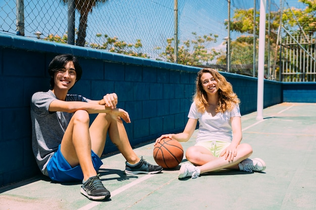 Happy teenagers sitting in basketball pitch